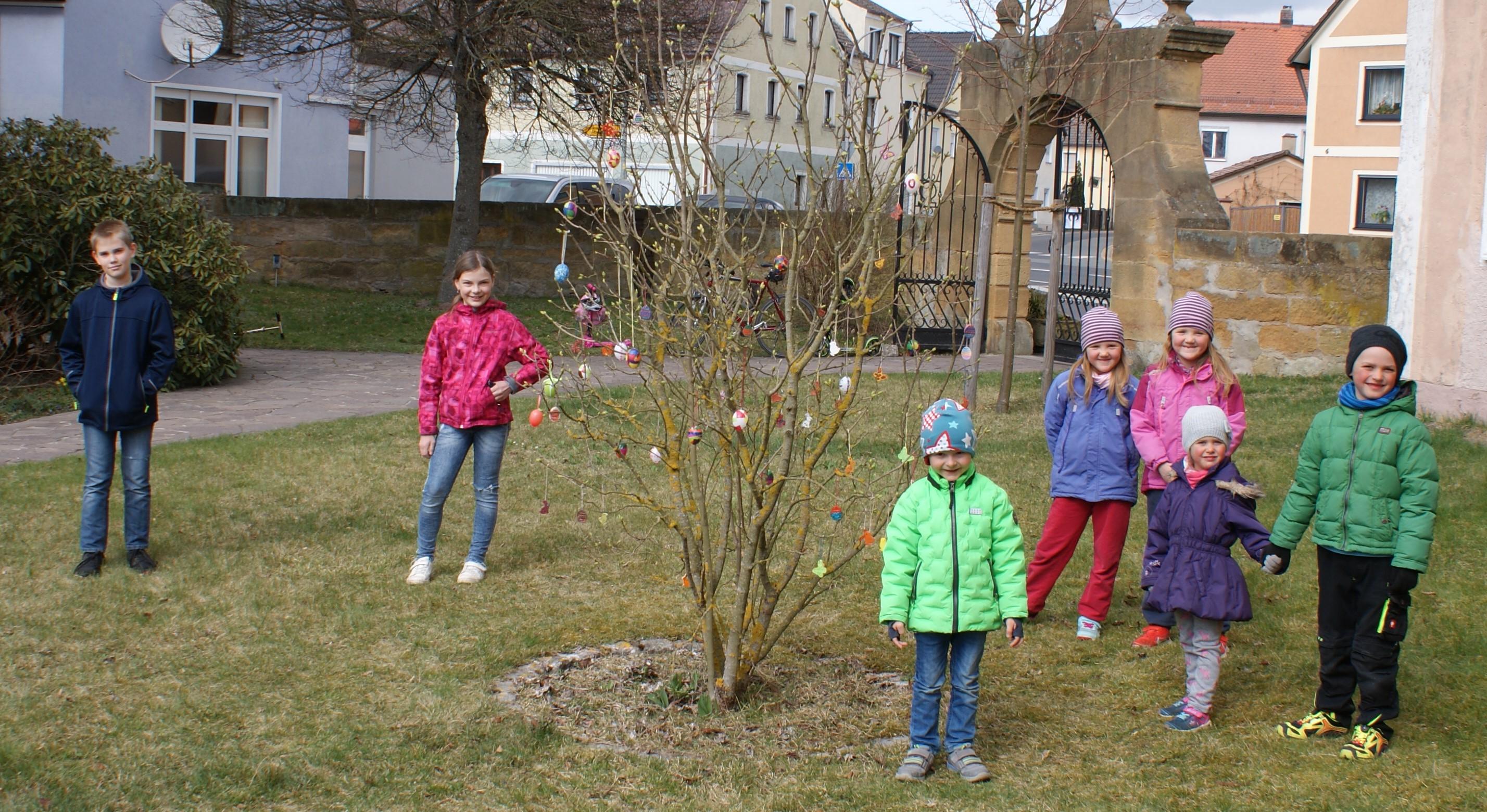 Kinder schmücken Strauch im Kirchgarten